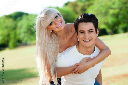 Cute couple piggybacking outdoors.