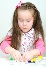 Cute undistracted girl sculpting using clay