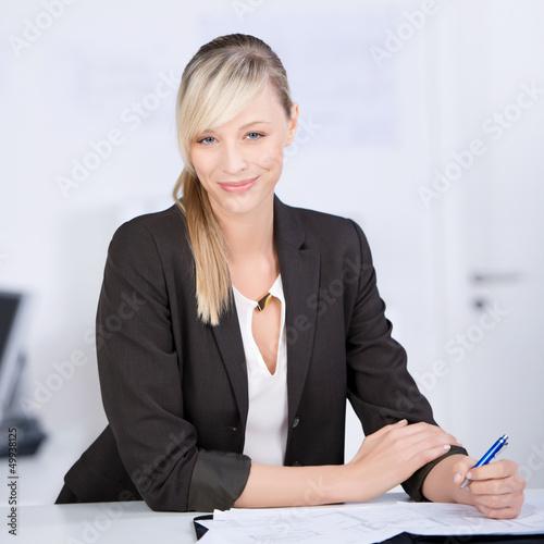 lächelnde geschäftsfrau schreibt in unterlagen