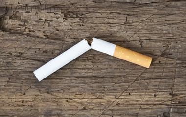 Zerbrochene Zigarette auf Holzplatte