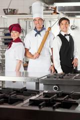 Confident Chefs And Waiter In Kitchen