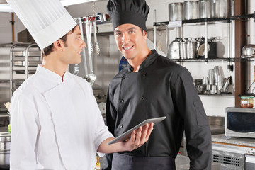 Chef With Colleague Holding Digital Tablet