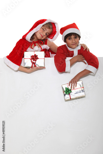 Brother and sister dressed in Santa Claus outfits