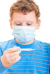 Мальчик в защитной маске с термометром в руках