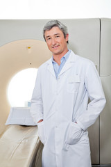 Doctor Standing Next To CT Scanner