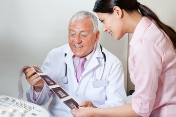 Doctor And Patient Looking At Ultrasound Print