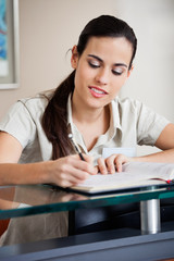 Female Receptionist Writing In Book