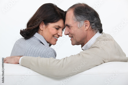 Married couple sat face to face on sofa