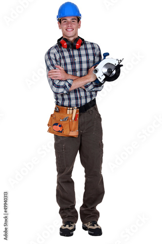 Portrait of a young tradesman holding a circular saw