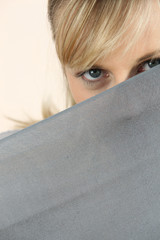 Young blond woman observing behind sheet