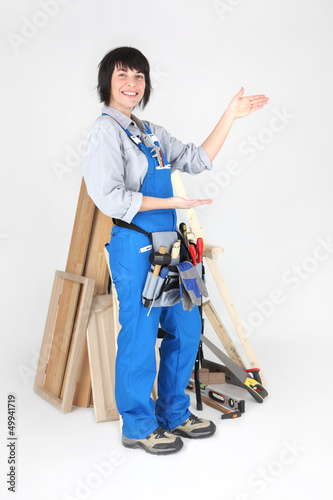 Female carpenter indicating the space to her side