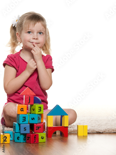 Pensive little girl near toys