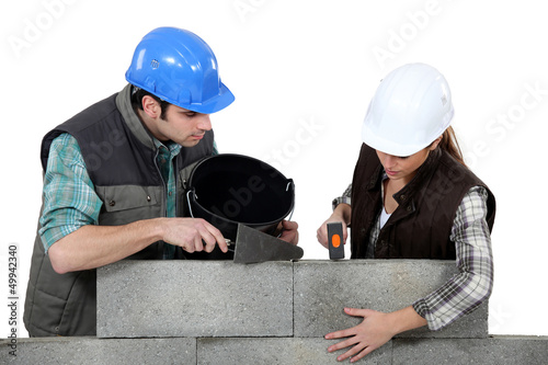 craftsman and craftswoman applying cement