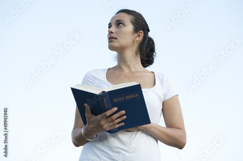woman with bible looking up