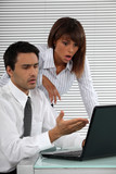 Two businessworkers shocked by laptop screen