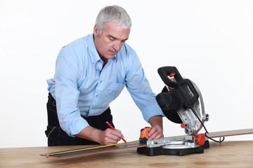 A senior carpenter with a circular saw.