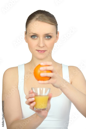 young woman pressing an orange