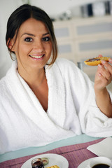woman in bathrobe having breakfast