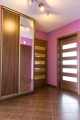 Purple hall interior with wardrobe and brown tiles