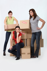 Three woman stood by pile of boxes