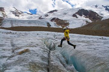 Alpinista che salta Crepaccio