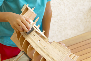 Enfant fabriquant un modèle réduit de galion