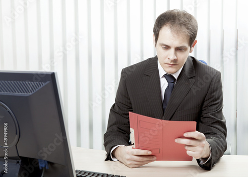 Worried businessman reading a document at his desk