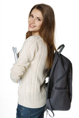 Happy woman wearing backpack and holding notebooks