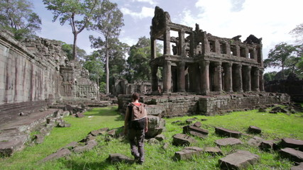 Backpacker walking in preah khan temple, angkor, cambodia