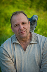 Man with parrot sitting on the shoulder .