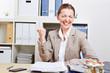 Jubelnde Frau im Büro ballt ihre Faust