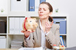 Frau im Büro tadelt ihr Sparschwein
