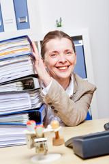 Frau im Büro mit vielen Akten