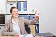 Frau im Büro berührt unsichtbaren Touchscreen