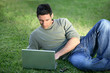 Man with laptop laying in field
