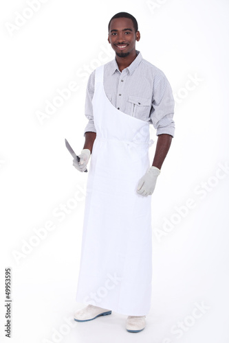 Full length studio portrait of a butcher with apron and knife