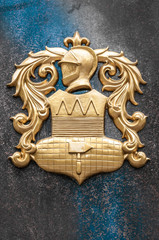 Gold arms with knight image on granite wall.