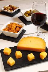 Vino, queso, aceitunas, galletas saladas y frutos secos