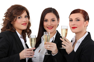 three elegant women drinking champagne
