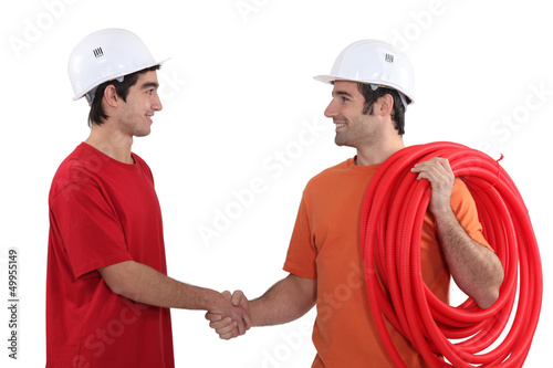Two electricians shaking hands