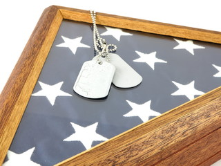 Vintage military dog tags on wood flag case and American Flag