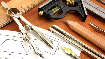 Vintage engineering and drafting tools on wood background.