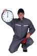 Plumber holding up a clock