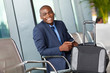 happy african american businessman waiting by airport