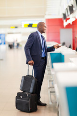 african businessman standing by airport check in counter