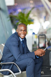 happy male african business traveller in airport