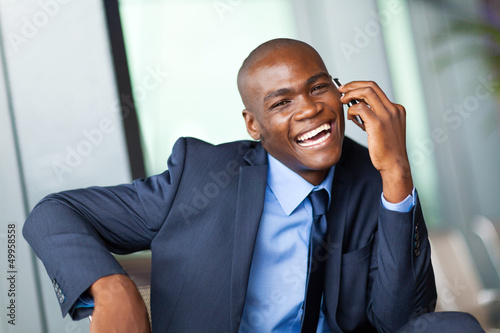 happy african corporate worker talking on cell phone