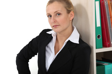 Businesswoman leaning against bookshelf