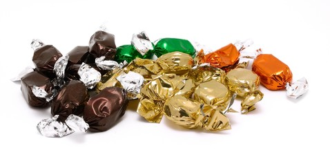 Packed candies in different color placed on a white background.