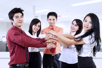 Business team joining hands in office